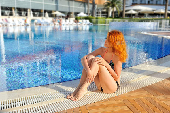 Sexy model in bikini near swimming pool with blue water - Stock Photo - Images