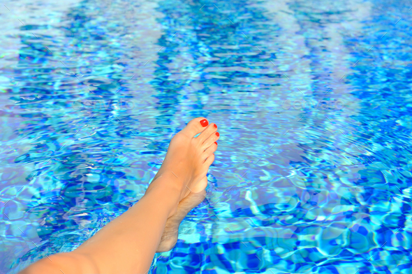 Woman feet in swimming pool on a hot summer day - Stock Photo - Images
