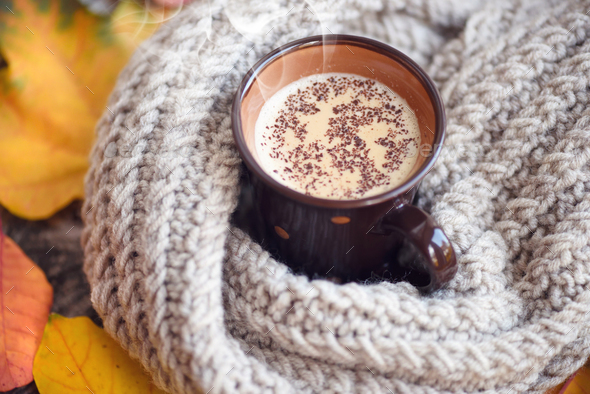 Autumn leaves, hot cup of coffee and a warm scarf on wooden tabl - Stock Photo - Images