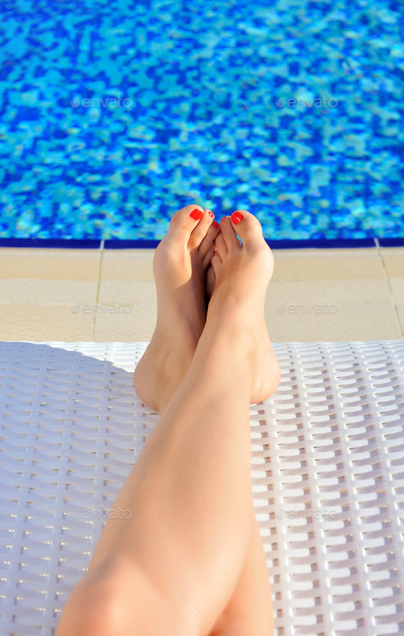 Woman legs with red nails on a lounger near the pool - Stock Photo - Images