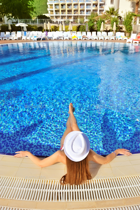 Beautiful woman white hat and bikini lying in a pool - Stock Photo - Images