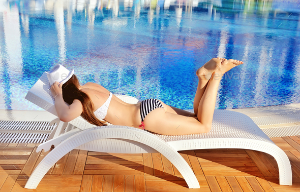Woman in white hat lying on a lounger near the swimming pool. Su - Stock Photo - Images