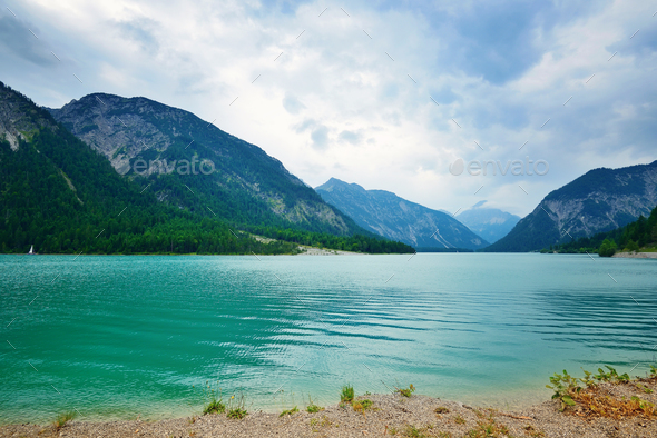 View into beautiful mountain lake in the Alps on a cloudy day - Stock Photo - Images