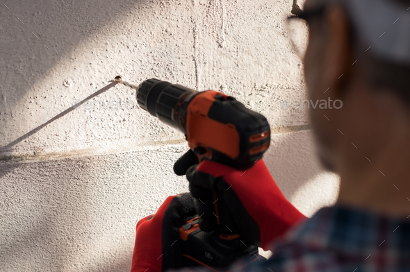 Man drilling hole in wall - Stock Photo - Images