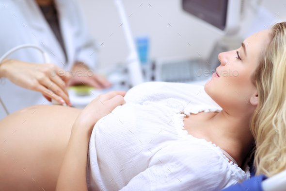 Pregnant woman doing ultrasound scan - Stock Photo - Images
