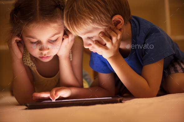 Two little kids watching cartoons - Stock Photo - Images