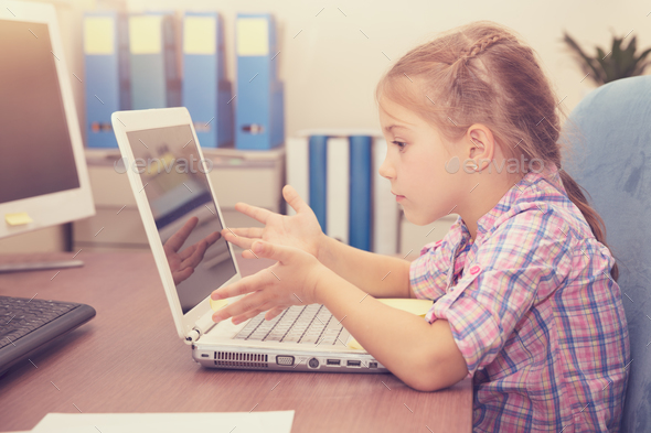 Little girl doing homework on the laptop - Stock Photo - Images
