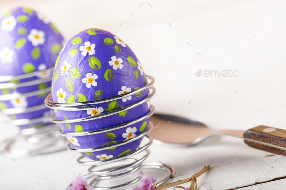 Wire egg cups with painted easter eggs on white table - Stock Photo - Images