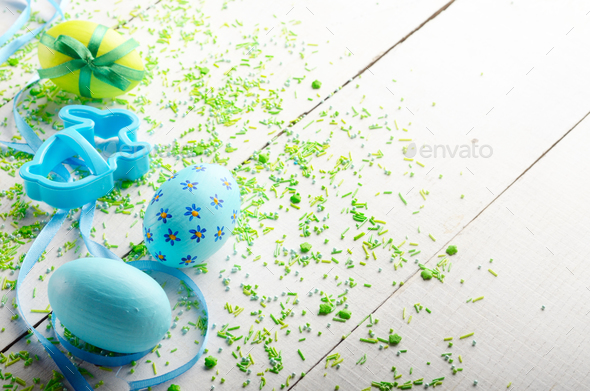 Coockie cutter in shape of easter bunny with painted eggs on whi - Stock Photo - Images