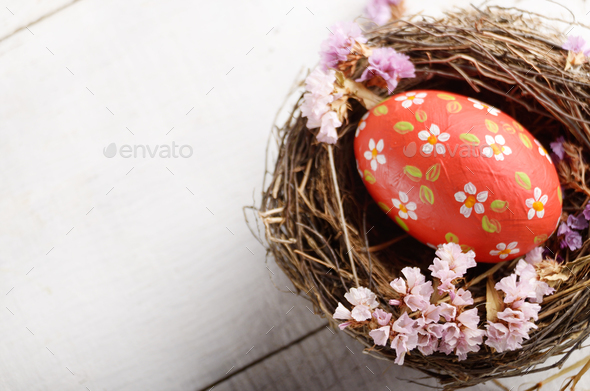 Rustic style painted red easter egg in the nest on white table - Stock Photo - Images