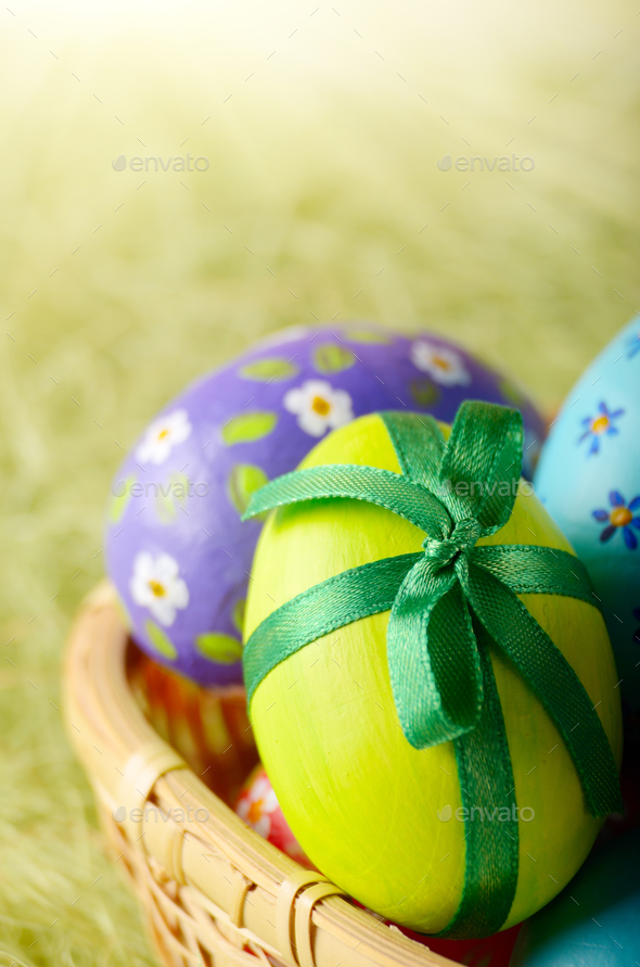 Rustic style painted easter eggs in basket on green background - Stock Photo - Images