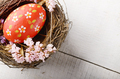Rustic style painted red easter egg in the nest on white table - PhotoDune Item for Sale