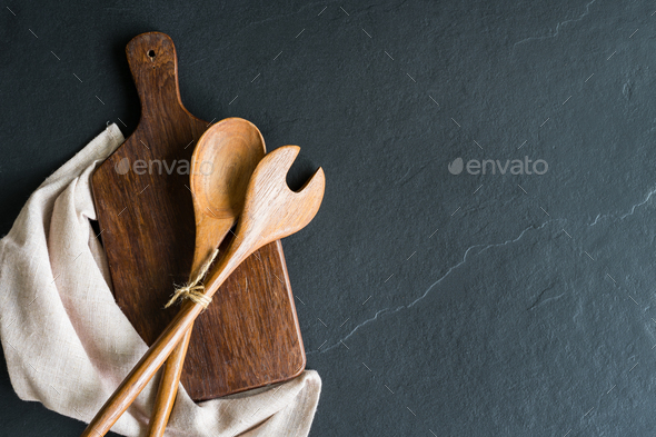 Old wooden cutting board on black stone background - Stock Photo - Images