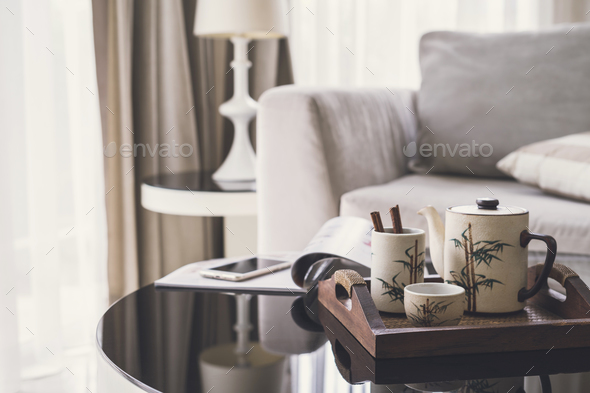 cup of tea on wooden tray on a round table with sofa in living room - Stock Photo - Images