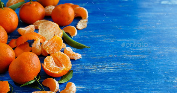 Mandarins with leaves on a bright blue background - Stock Photo - Images
