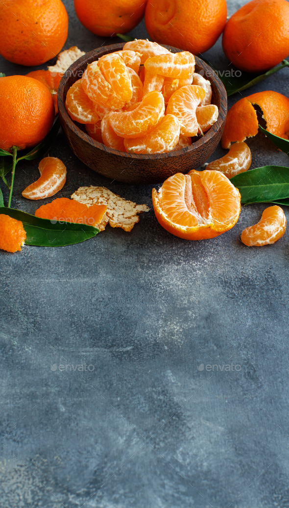 Mandarins with leaves in a bowl on a grey  background - Stock Photo - Images