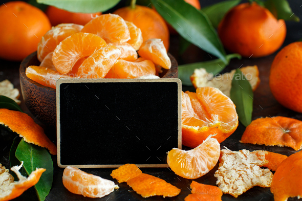 Mandarins in a bowl with a small chalkboard on a dark background - Stock Photo - Images