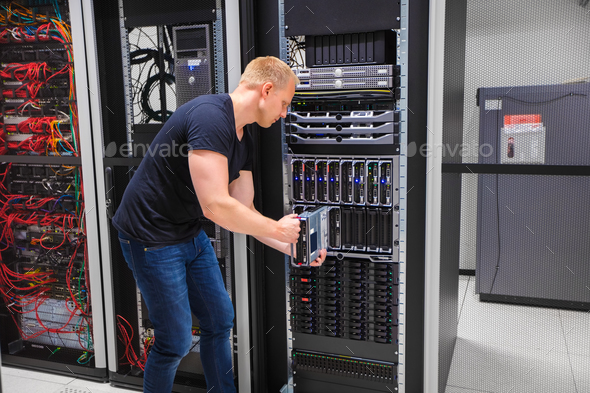 Computer Engineer Installing Server Into Blade Enclosure - Stock Photo - Images