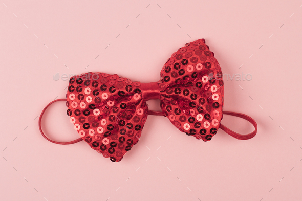 red bow tie with spangles on light pink background - Stock Photo - Images