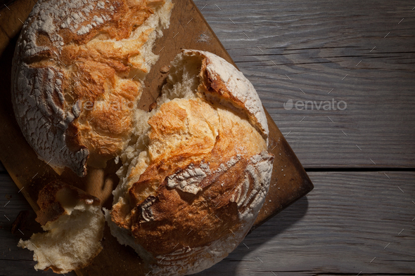 Torned homemade bread loaf on old cutting board with a free space on the right - Stock Photo - Images