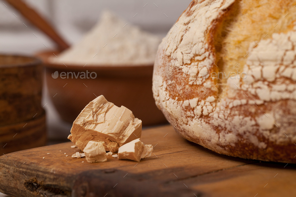 Homemade bread on old cutting board with a pile of fresh yeast - Stock Photo - Images
