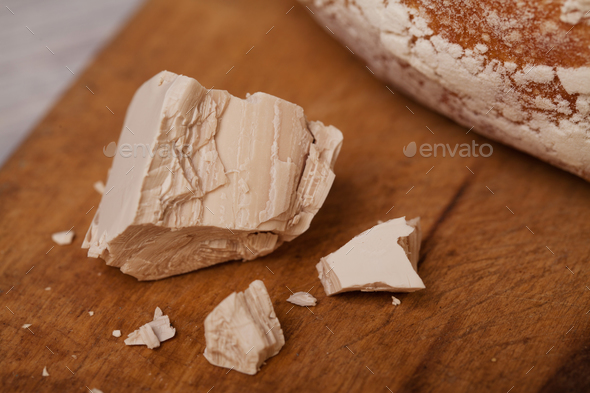 A pile of fresh yeast with a Homemade bread on old cutting board - Stock Photo - Images