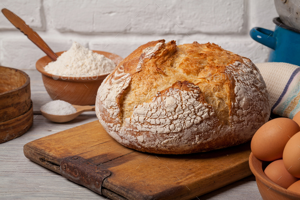 Homemade bread on old cutting board - Stock Photo - Images