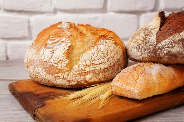 Fresh homemade bread assortment on old cutting board - Stock Photo - Images