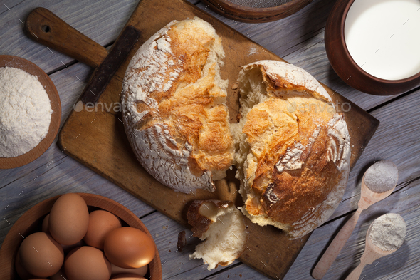 Torned homemade bread loaf on old cutting board with cooking ingredients. - Stock Photo - Images