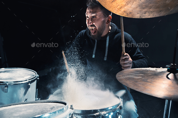 Drummer rehearsing on drums before rock concert. Man recording music on drum set in studio - Stock Photo - Images