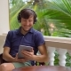 Man in Tropics Talking with Friends and Family on Video Call Using a Tablet and Wireless Headphones - VideoHive Item for Sale