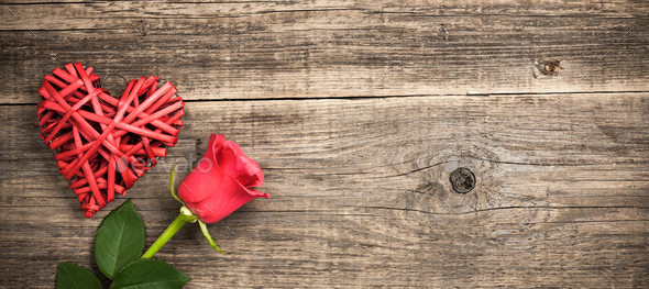 Red wicker heart and rose flower on wooden background - Stock Photo - Images