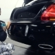 A Man Polishes a Black Car with a Polisher - VideoHive Item for Sale