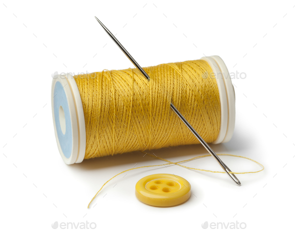 Yellow bobbin, needle and sewing button - Stock Photo - Images