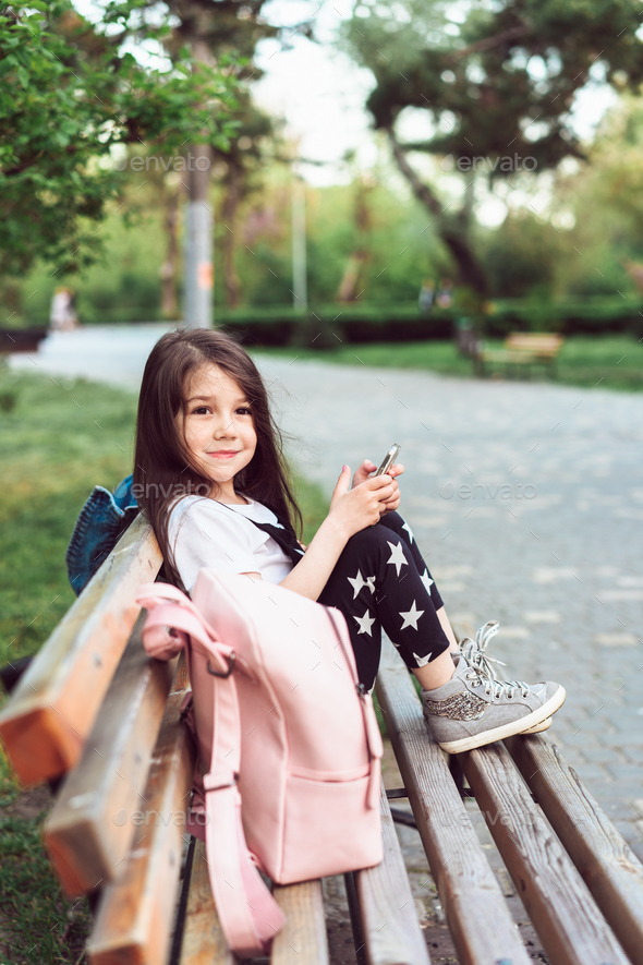 little girl with a smartphone sitting on a bench - Stock Photo - Images