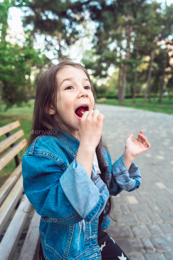 Girl sitting on bench with candies - Stock Photo - Images