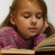 View of a Girl Reading a Book. A Young Cute Girl Reads a Book in a Whisper - VideoHive Item for Sale