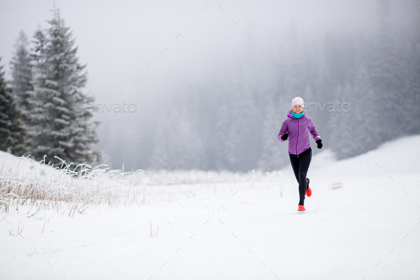 Trail running girl in winter mountains - Stock Photo - Images