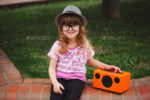 little hipster girl listens music on wireless retro looking spea - Stock Photo - Images