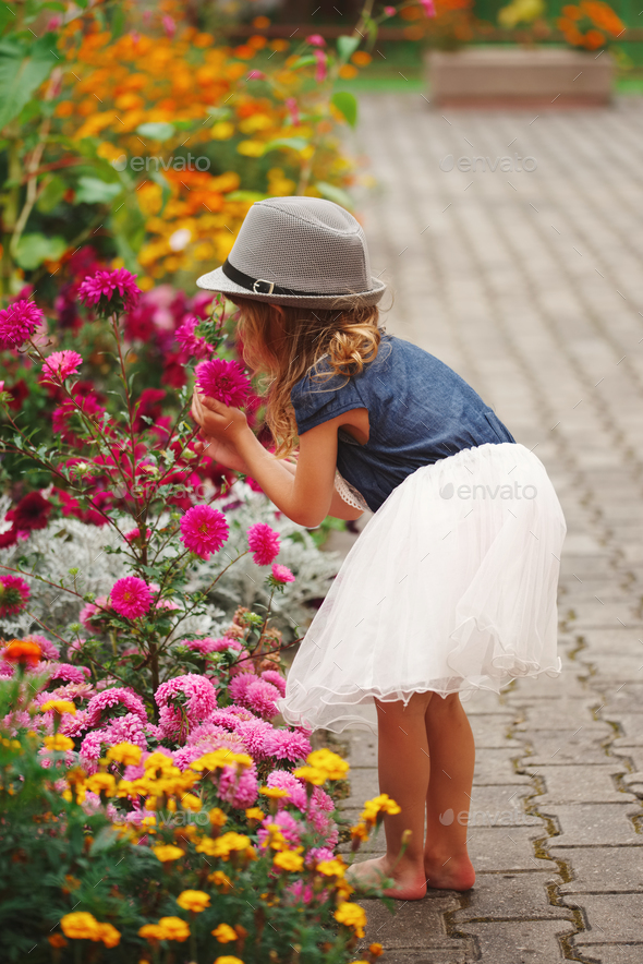 little beautiful girl in flowers park - Stock Photo - Images