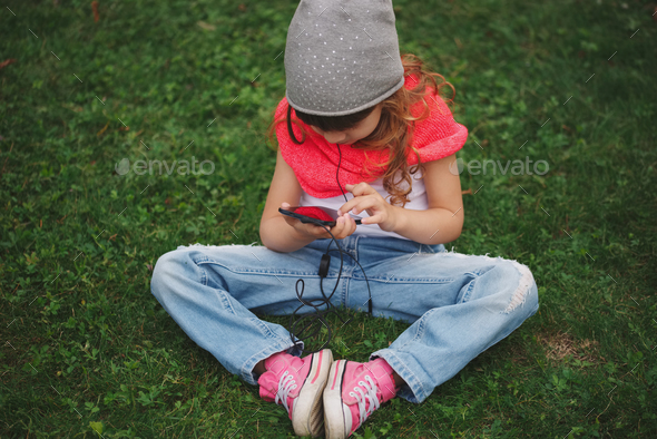 little girl with mobile phone on the grass - Stock Photo - Images