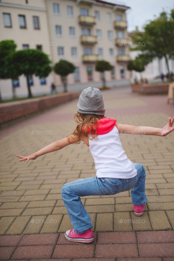 little girl dancing on the street - Stock Photo - Images