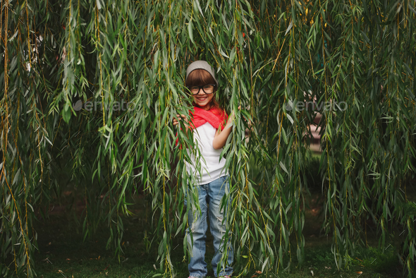 little girl hiding in the willow foliage - Stock Photo - Images
