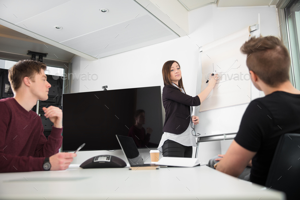 Businesswoman Explaining Graph On Flipchart To Male Colleagues - Stock Photo - Images