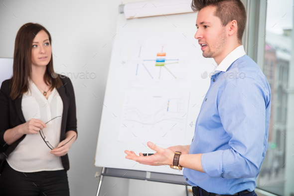 Businessman Giving Presentation While Colleague Looking At Him - Stock Photo - Images