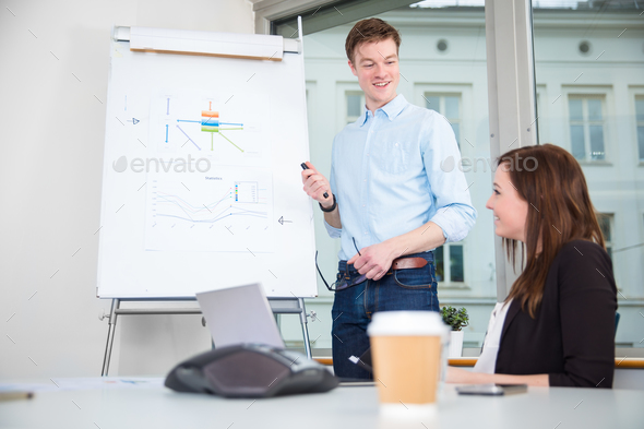 Smiling Businessman Giving Presentation To Colleague In Office - Stock Photo - Images