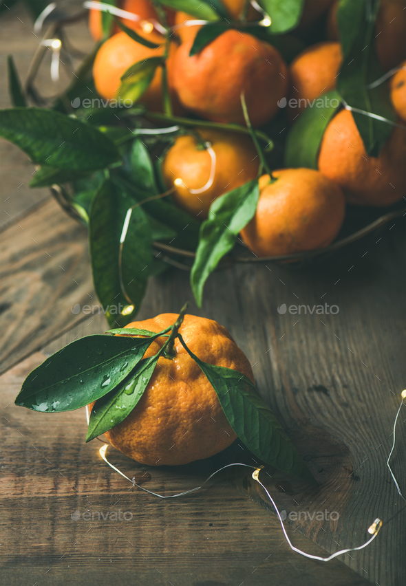 Fresh tangerines with leaves and light garland - Stock Photo - Images