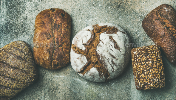 Top view of bread loaves over grey concrete background - Stock Photo - Images