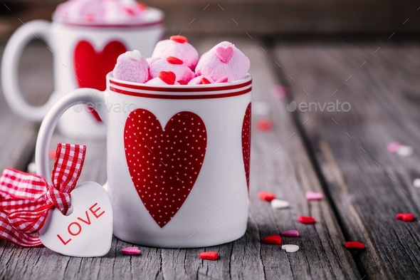 Hot cocoa with pink marshmallow in mugs with hearts for Valentine's day - Stock Photo - Images