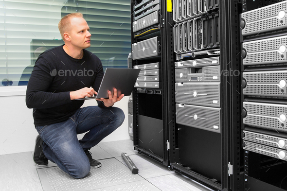 Consultant Using Laptop While Monitoring Servers In Datacenter - Stock Photo - Images